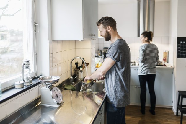 Man washing pan while woman standing in background in kitchen