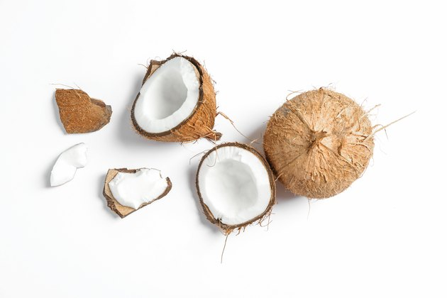 Two coconut one of which split on white background