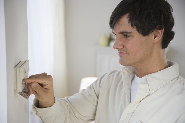Man adjusting digital thermostat