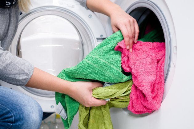 Midsection Of Woman Putting Clothes In Washing Machine