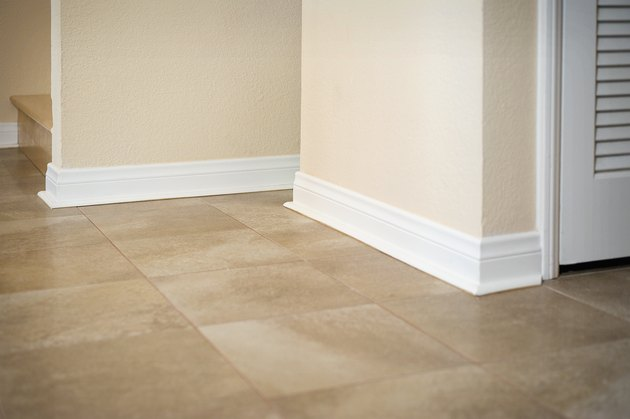 White baseboard along ceramic tile floor