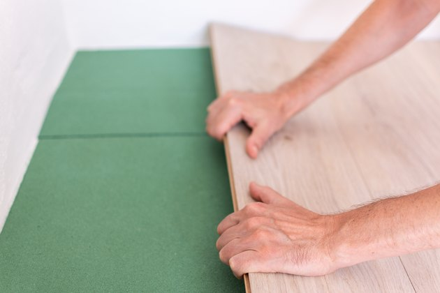 Worker installing wooden laminate flooring