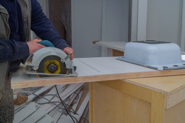 Contractor cuts the countertop for sink furniture on the kitchen electric saw