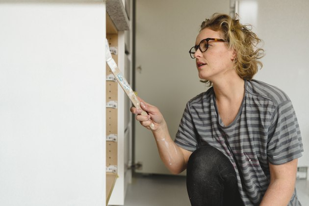 Woman painting cupboard
