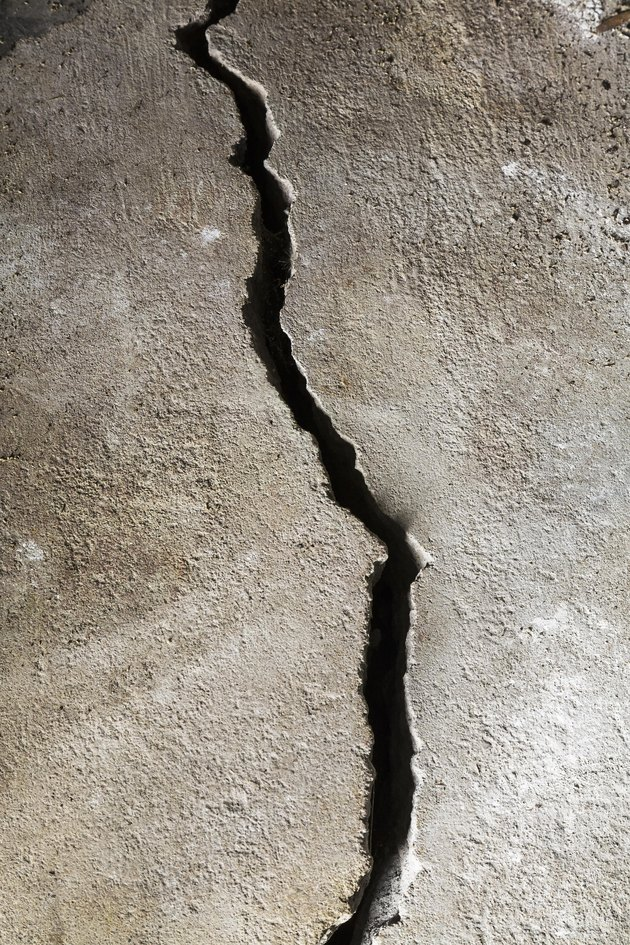 Close-up of a half-inch crack in a poured cement floor, background image