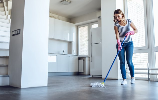Young woman is doing cleaning of a laminate floor