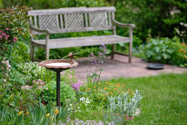 Idyllic green springtime garden with bench and bird bath