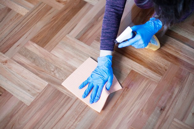 Woman cleaning parquet floor