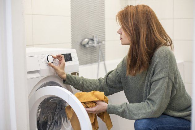 Young woman setting a washing machine