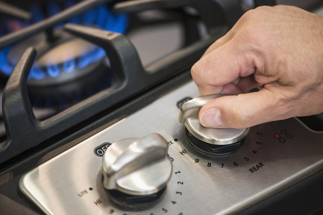 USA, New Jersey, Jersey City, Close-up of hand adjusting stove burner