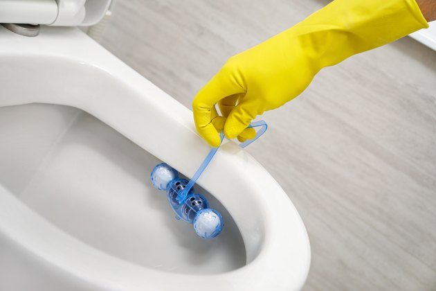 Putting toilet balls cleaner in toilet bowl