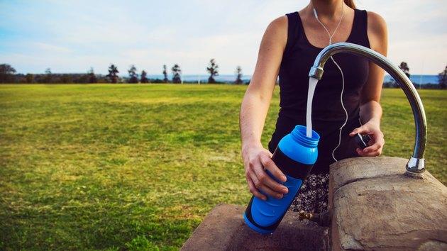Female runner fills up water bottle outdoors