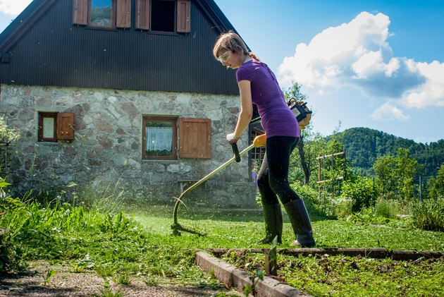 Woman Cutting  The Lawn  With  Weed  Trimmer