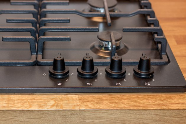 The control panel of the gas hob, the knob for adjusting the intensity of combustion of the gas stove burner. Black gas hob integrated into the wooden worktop