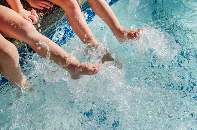 Children's feet splashing in pool water