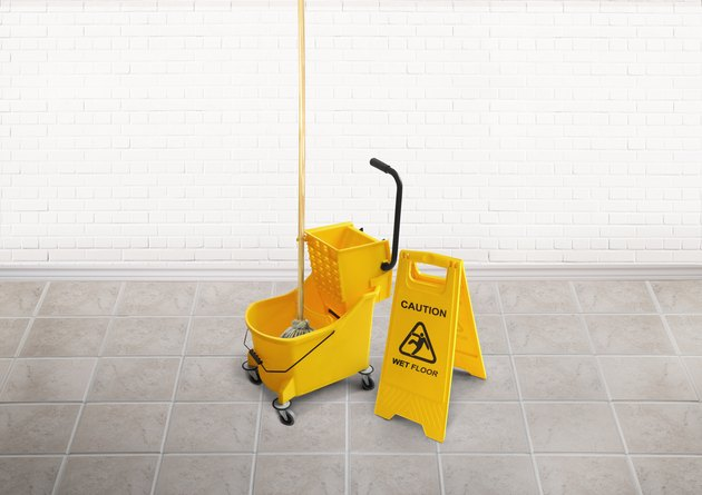 Cleaning bucket with mop and a wet floor slippery sign in an empty room