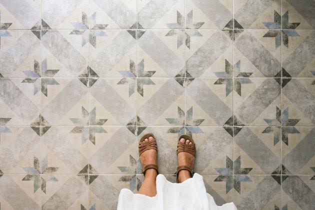 Woman standing on ornate tiled floor