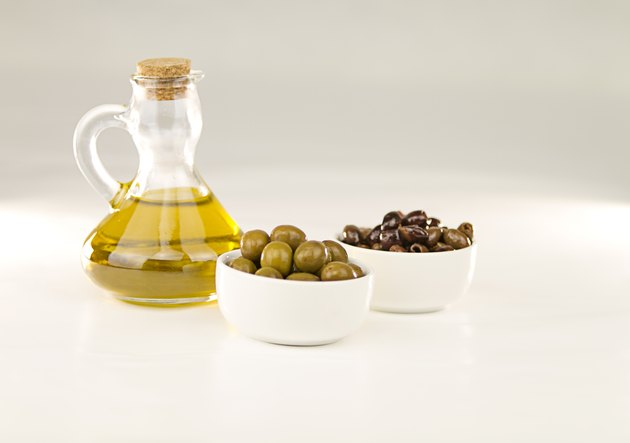 Close-up of a flask with extra virgin olive oil and two small cups with different varieties of olives on white background