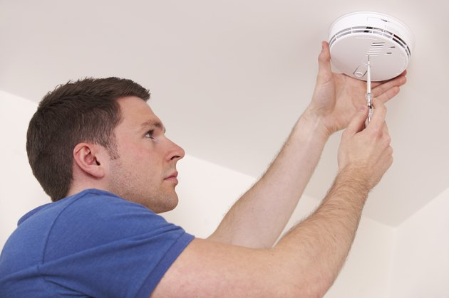 Man installing smoke or carbon monoxide detector.