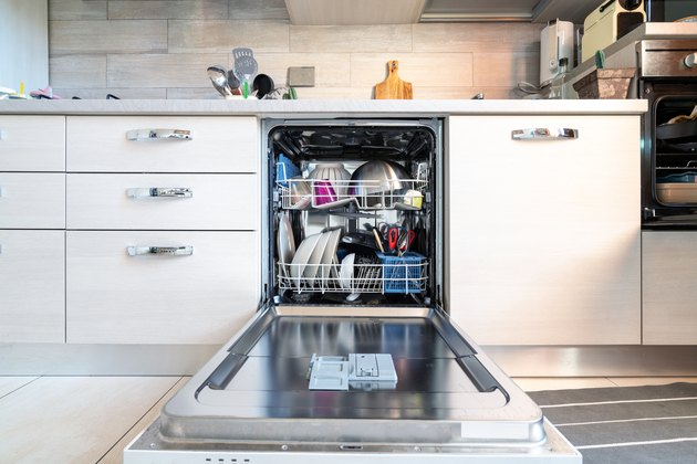 Opened dishwasher with clean dishes