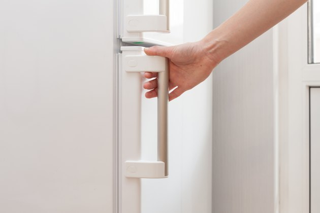 Hand of a young woman is opening a freezer door