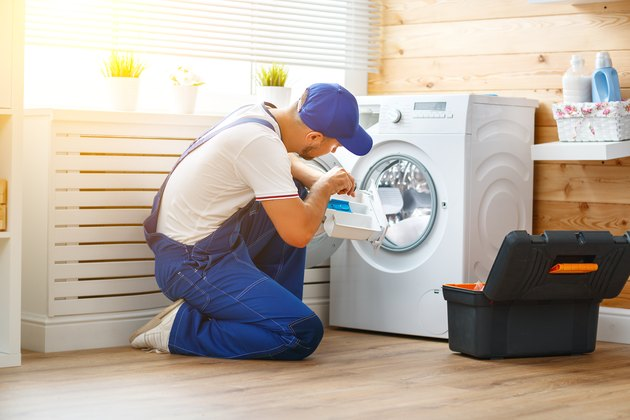 working man   plumber repairs  washing machine in   laundry