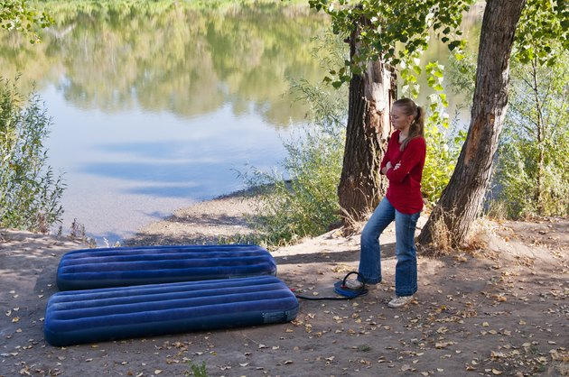 Rest at nature. Girl pumps up an inflatable mattress