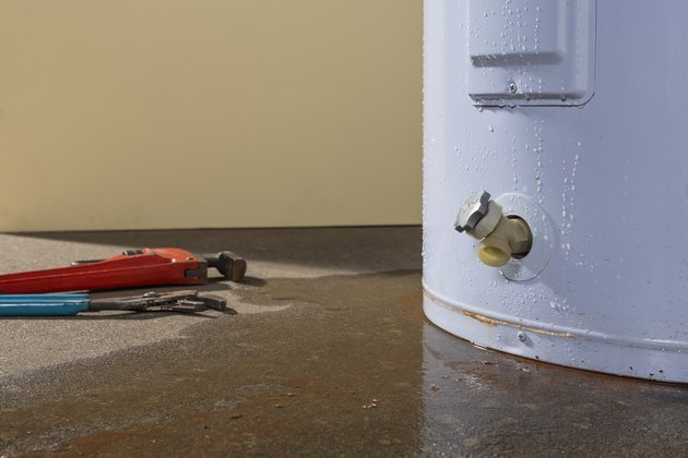 A residential domestic water heater leaking with plumber's tools
