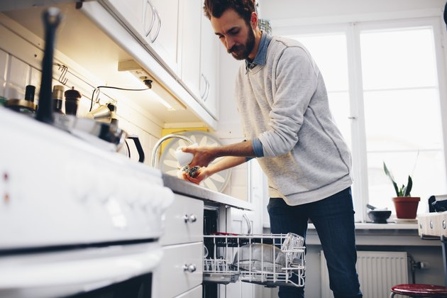 Man cleaning utensils in kitchen at home
