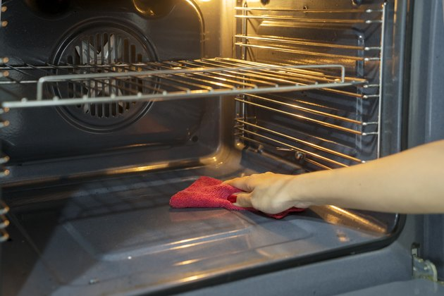 Cropped Hand Of Woman Cleaning Oven