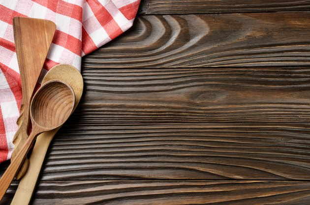 Red checkered napkin and wooden utencils on brown wooden kitchen table with copy-space. Top view