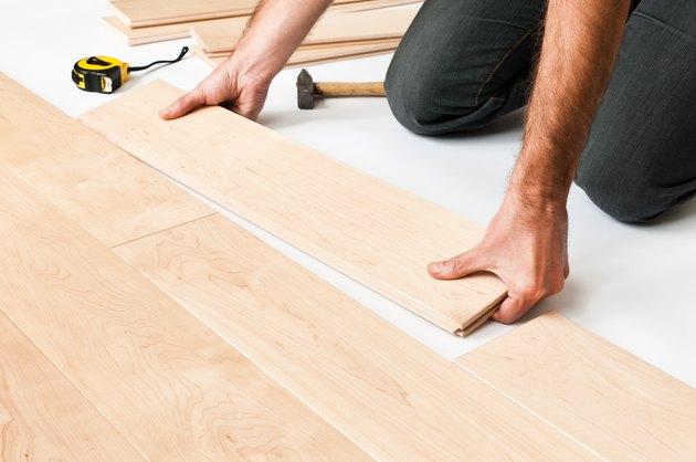 Close-up of man putting hardwood floor panels, floorboards