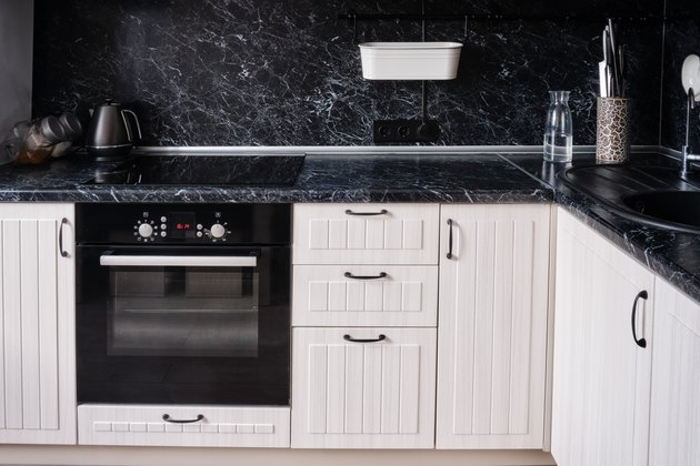 White wooden kitchen with black countertop and apron. Kettle, hob with oven