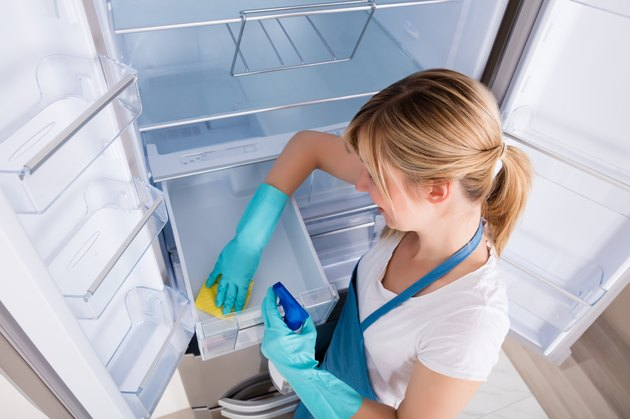 High Angle View Of Woman Cleaning freezer