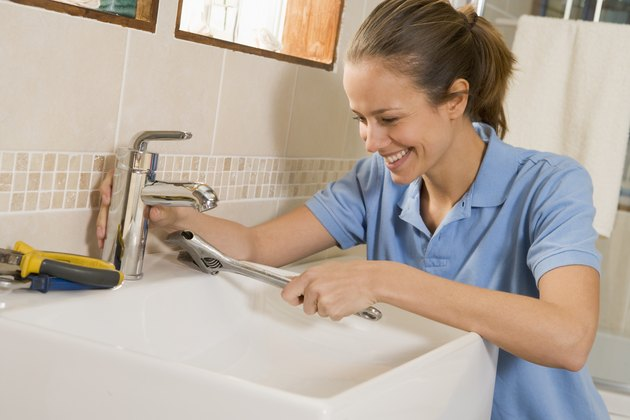 Woman working on sink.