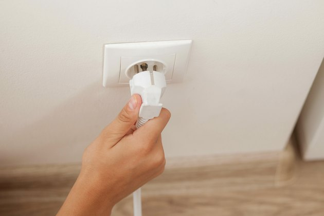 Hand plugging in or out an electric cord into a socket