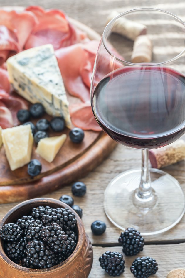 Red wine with berries, cheese and ham