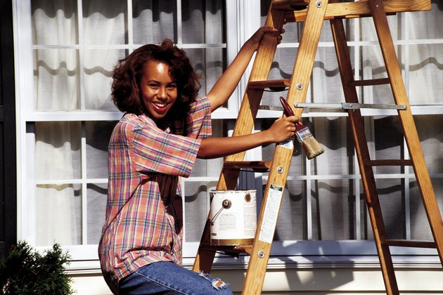 Young woman standing on ladder painting exterior of house