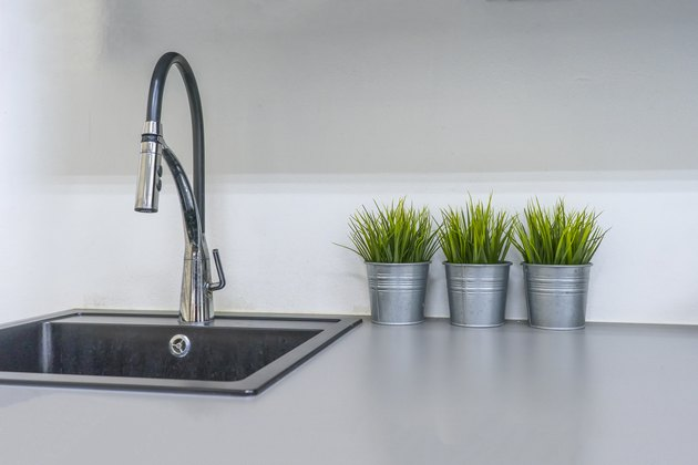 Kitchen sink and faucet in house interior.