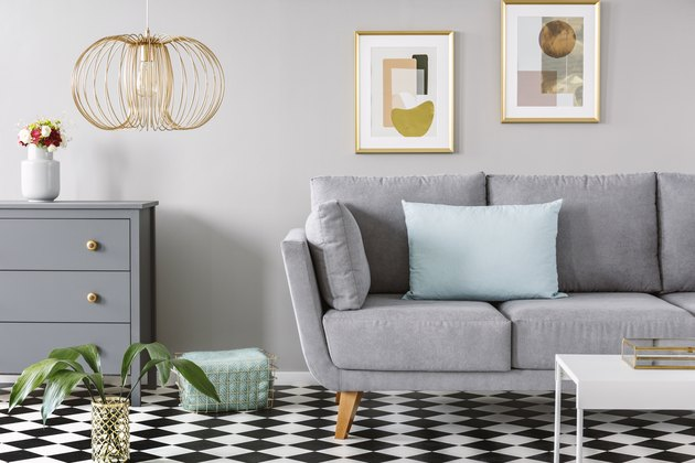 Light blue pillow placed on grey couch in bright living room interior with checkerboard linoleum floor, fresh flowers in vase on cupboard two posters hanging on the wall and gold lamp