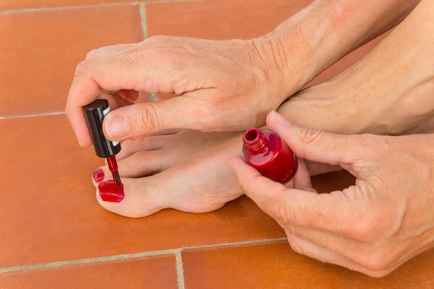Hands paint nails of toes red