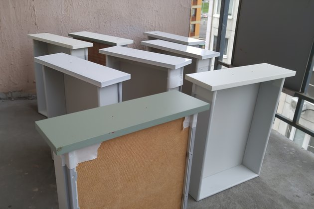 Painting the drawers of the cabinet and the bedside tables from the paint can. In white color. On the balcony.