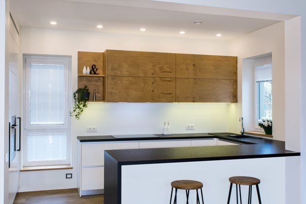 Modern kitchen design in light interior with wood accents.