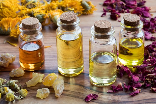 Bottles of essential oil with dried rose petals, chamomile, calendula and frankincense