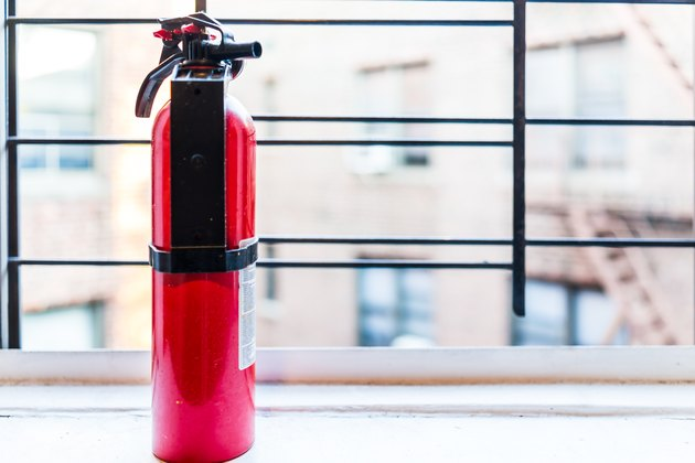 Small apartment red fire extinguisher safety by window in New York City NYC urban Bronx, Brooklyn brick housing, guard rail, security bars