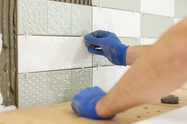 Installing ceramic tiles on the wall in kitchen. Placing tile spacers with hands, renovation, repair, construction.