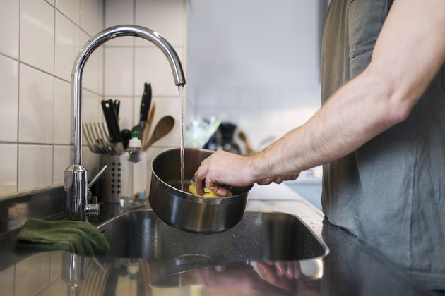Midsection of man washing sauce pan with scouring pad at sink