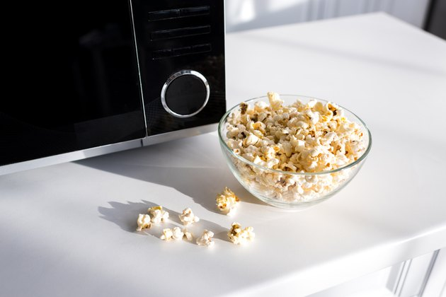 popcorn in bowl near microwave on table in kitchen