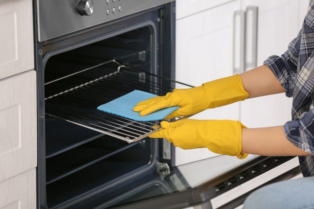 Woman cleaning oven in kitchen, closeup