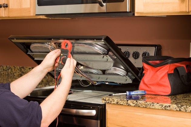 Appliance Repairman Using Multimeter on a Kitchen Range